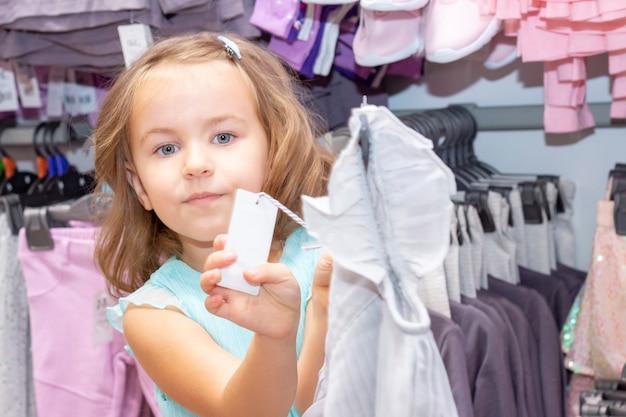 ショッピング。割引。少女中毒者。店先からの美しいドレスに喜んでいる少女。ショッピングセンター、ショッピング。感情。値札を示します