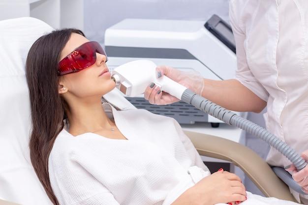 ビューティーサロンでの光脱毛の手順。ビューティーセンターで顔に脱毛レーザー治療を受ける若い女性をクローズアップ