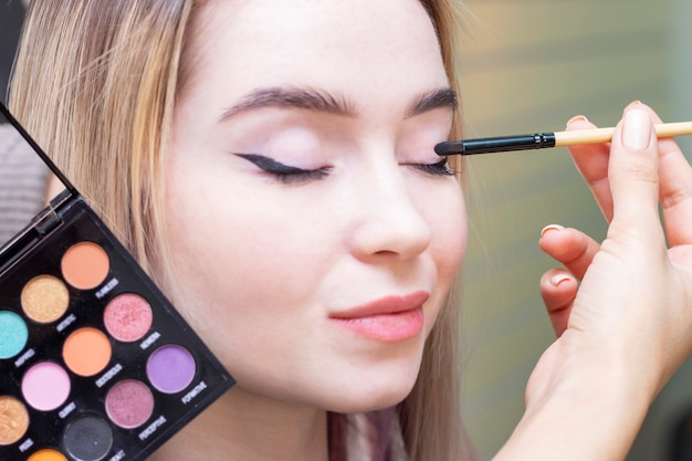 Визажист наносит макияж на глаза девушки. палитра теней. салон красоты. крупный план