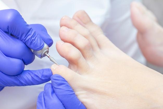 Терапевтический педикюр. мастер-подолог занимается аппаратным педикюром. посещение подиатрии. лечение ног в спа-салоне. клиника подиатрии.