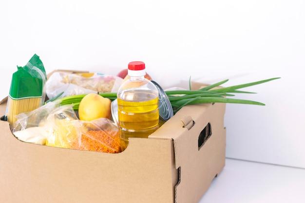 寄付。食料品の箱、困っている人に製品を助けます。募金箱。白い表面に食品の必需品と段ボール箱。