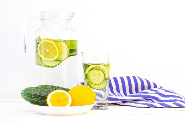 ヘルスケア、フィットネス、健康的な食事のコンセプトです。水、カクテル、デトックスドリンク、ガラスの水差しとガラスのレモネードと新鮮なクールなレモンキュウリドリンク。きゅうりとレモンプレート