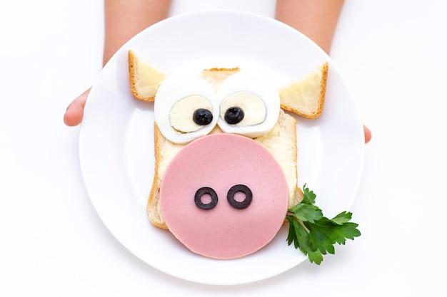 サンドイッチ牛。子供の手には、朝食または昼食用のサンドイッチが付いた白い皿があります。