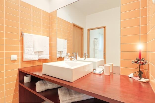 洗面台と照明付きキャンドルを備えたバスルーム。
