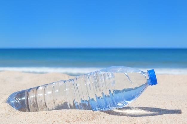 Бутылка прохладной воды на пляже у моря.