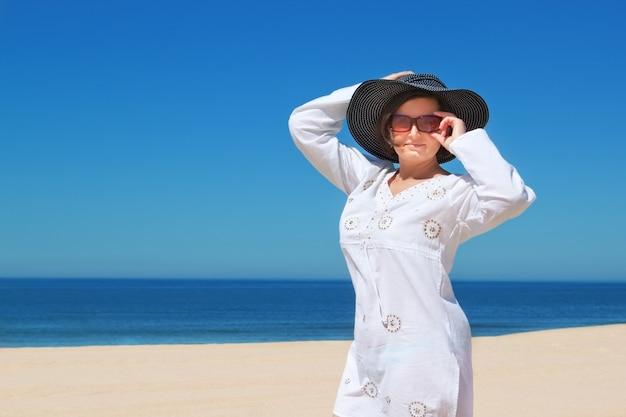 ビーチの帽子の美しい少女。