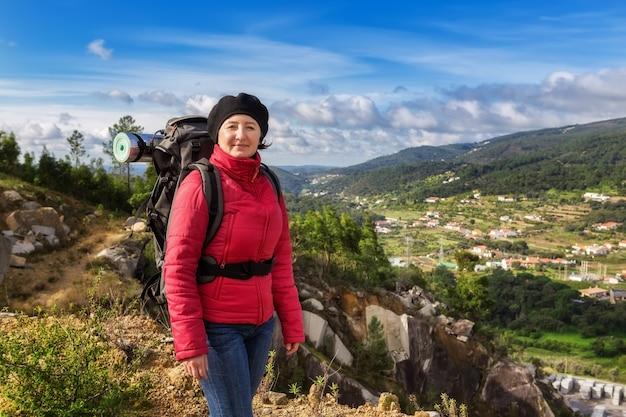 Девушка турист с рюкзаком в походе. с видом на моншику.
