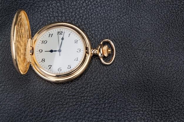Золотые карманные часы на фактурной коже. крупный план.