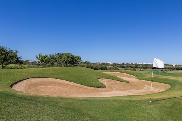 白い旗のあるゴルフコースのサンドトラップ。