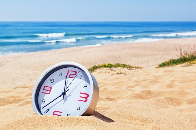 海の近くのビーチの砂の中の古典的なアナログ時計。休日に。