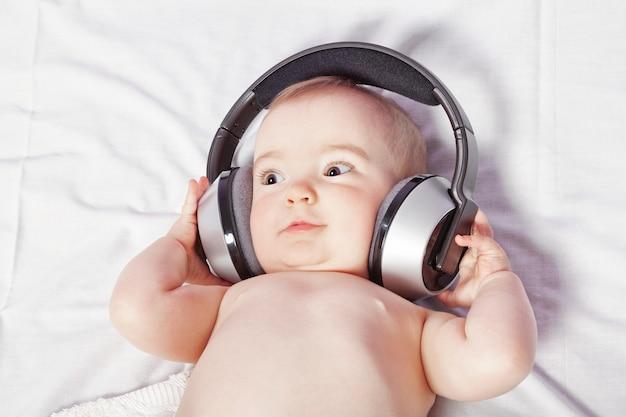 ワイヤレスヘッドフォンで音楽を聴いて横になっている女の赤ちゃん。閉じる。