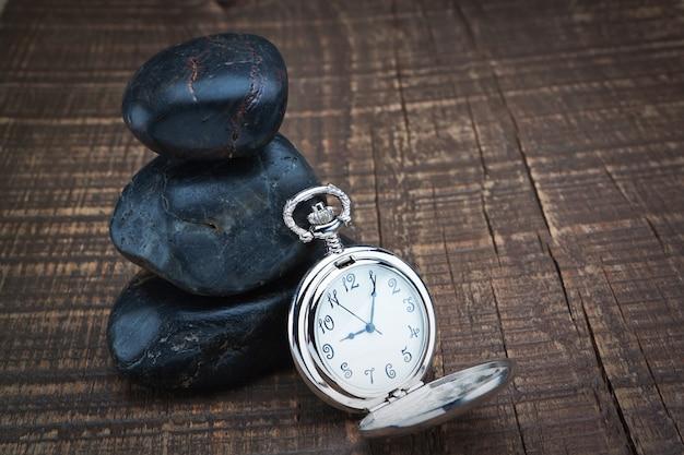 スパの石の近くの懐中時計。木製のテクスチャ。