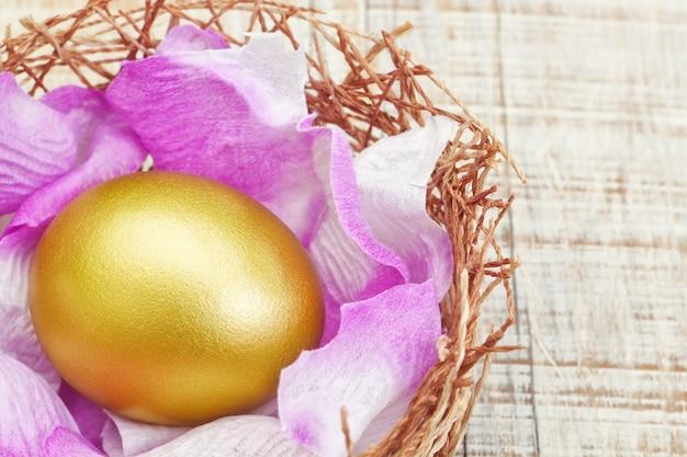 紫色の花びらを持つ巣の黄金の卵。