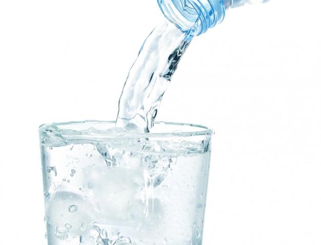 В стакан со льдом течет чистая вода. на белой стене.