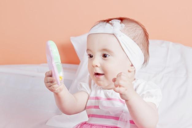 Детка девочка играет с игрушкой сюрприз. один год.