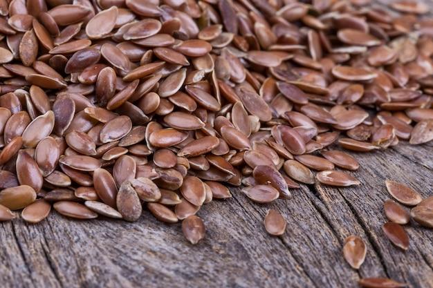 茶色の穀物の亜麻のクローズアップ。テクスチャの木製の背景。