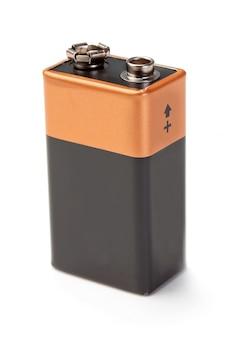 端子付きの新しいバッテリー。白い壁の上。