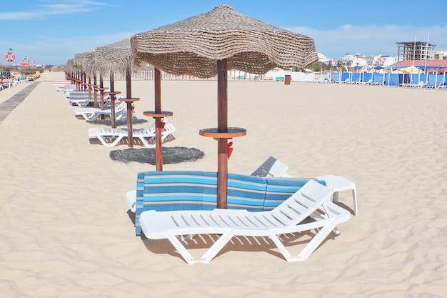 太陽が降り注ぐビーチの行に木製のビーチパラソル。残りのため。