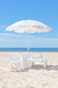 太陽が降り注ぐビーチの美しい白いビーチパラソル。残りのため。