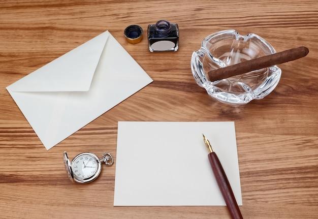 Композиция на столе еще не закончена письмом, конверт, сигара и ручка.