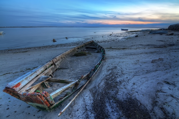 Старая покинутая сломанная шлюпка на море против ландшафта моря.
