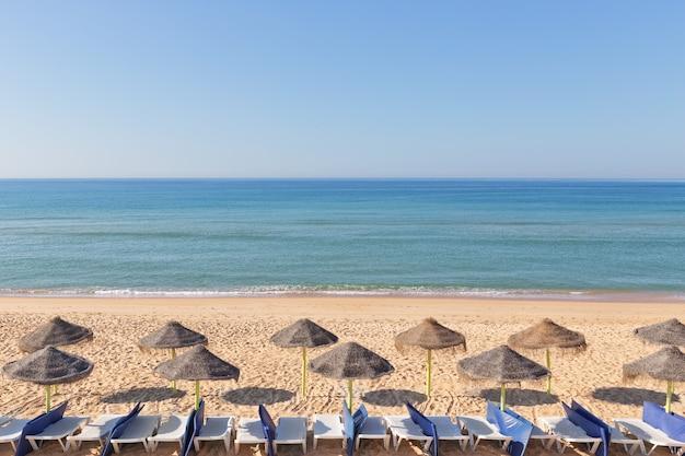 Экзотический пейзаж с зонтиками на пляже возле пляжа. в португалии.