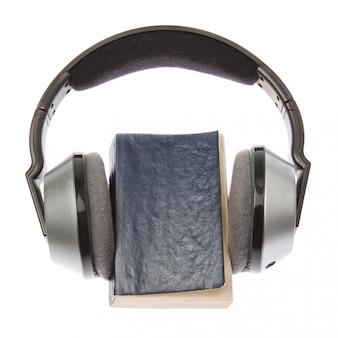ワイヤレスヘッドフォンと本。白い壁の上。