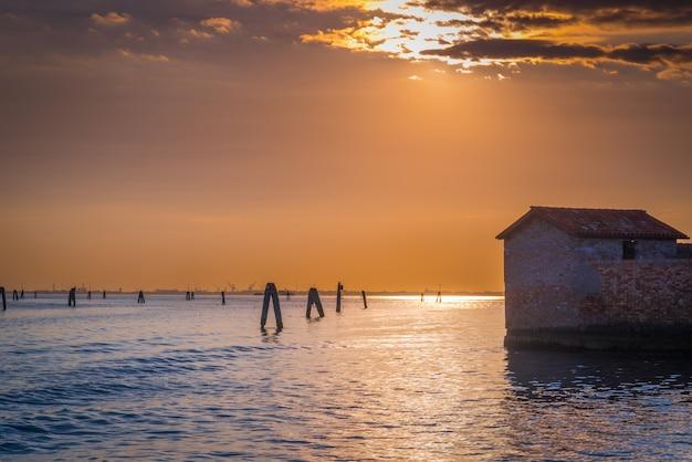 日没時のヴェネツィアのラグーンのパルド島のサンジャコモの古い放棄された建物