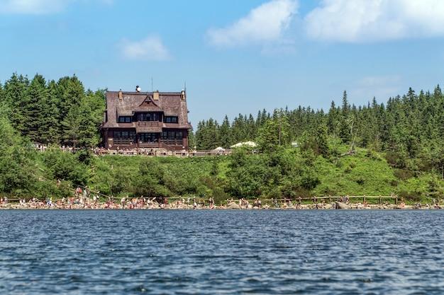 観光客の群衆とタトラの山の湖で小屋のビュー