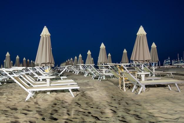 夜の人けのないビーチ。空のサンベッド。人のいないビーチ。