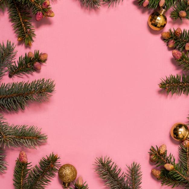 ピンクの背景にクリスマスツリーの枝。正月のコピースペース