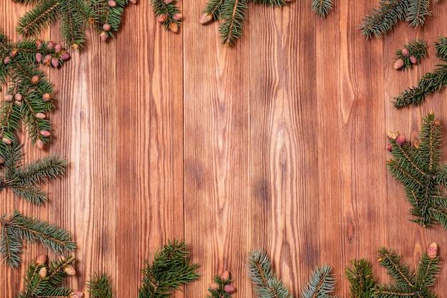 木製の背景にクリスマスツリーの枝。正月のコピースペース