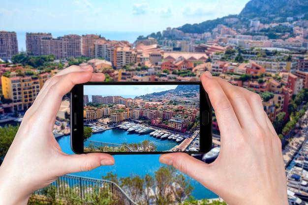 Вид на роскошные яхты и апартаменты в монако. турист фотографирует