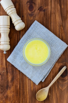 茶色の木製テーブルの上のボウルにギーバター。垂直方向、上面図。