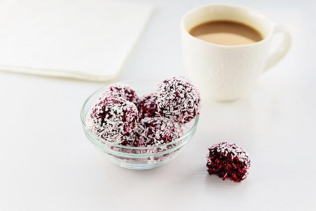 白いテーブルにコーヒーのカップとブラックカラント、ナッツ、ココナッツフレークのキャンディー