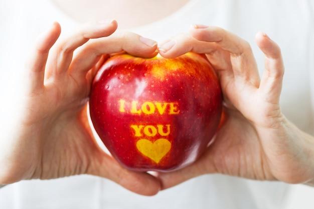 「私はあなたを愛して」という碑文が人の手にあるリンゴ。バレンタインデーのコンセプト。