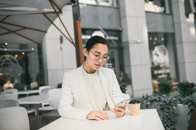 Молодая привлекательная азиатская бизнес-леди в стеклах сидит вне кофейни, выпивая кофе