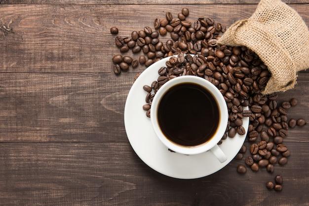 コーヒーカップと木製のテーブルの上のコーヒー豆。上面図。