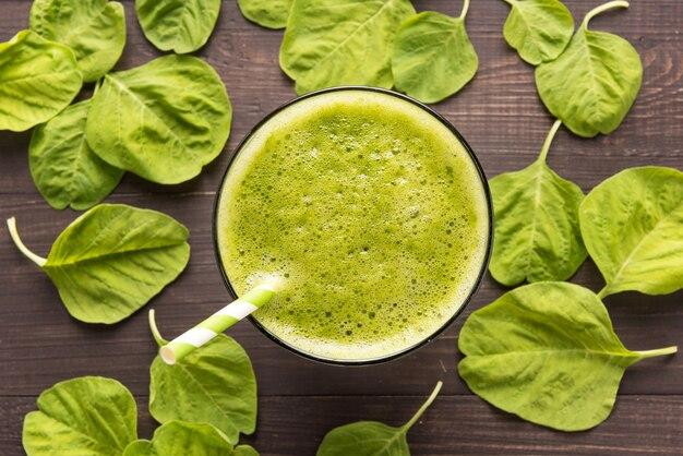 Здоровый зеленый коктейль на деревенском деревянном столе
