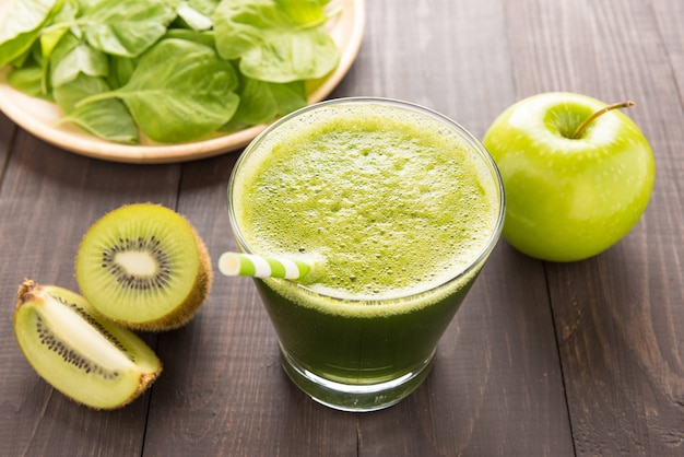 Здоровый зеленый коктейль с киви, яблоко на деревенском деревянном столе