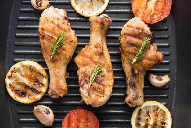 Жареная куриная ножка и овощи на сковороде