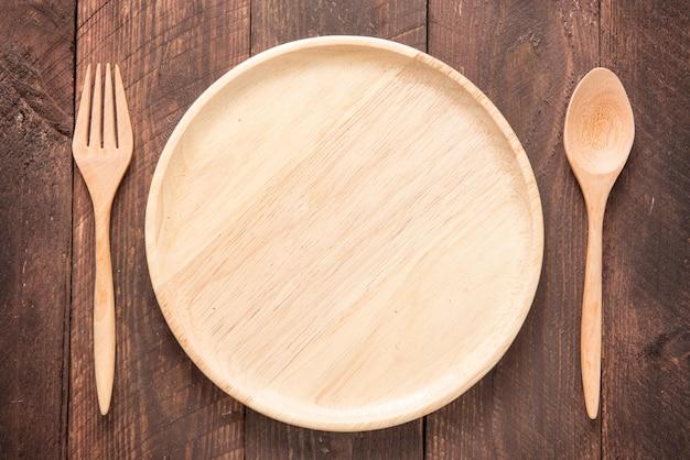 木製のテーブルにフォーク、スプーン、皿のセット