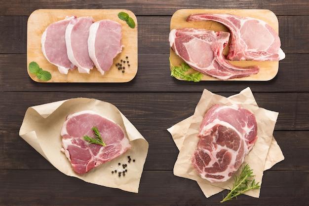 Установите сырое мясо на разделочную доску на деревянном фоне