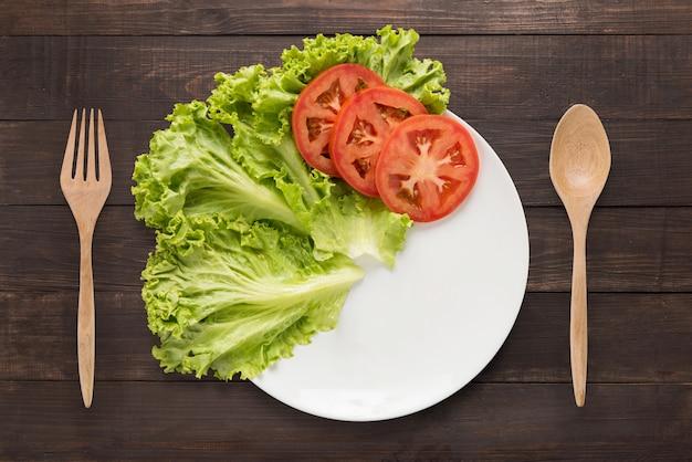 Пустая тарелка с помидорами и овощами в ожидании еды