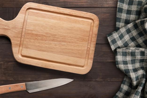 木製の背景に分離されたカッティングボードとナイフセット。テキストとロゴのコピースペース。上面図。