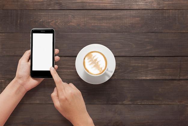 木製のテーブルでコーヒーの横にあるスマートフォンを使用してください。