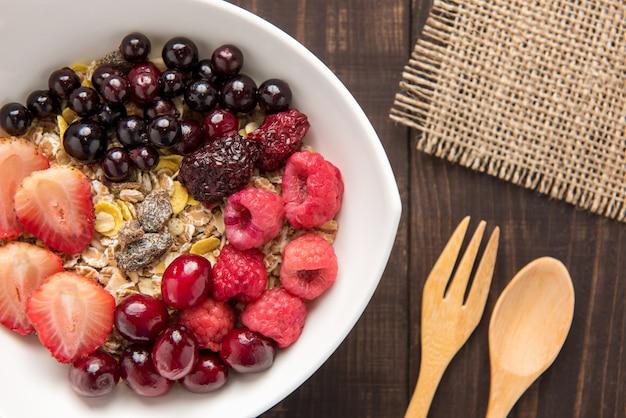 ヘルシーな朝食に新鮮なブルーベリー、クランベリー、イチゴ、ラズベリー、ブラックベリーをトッピングしたボウルのオートミール。
