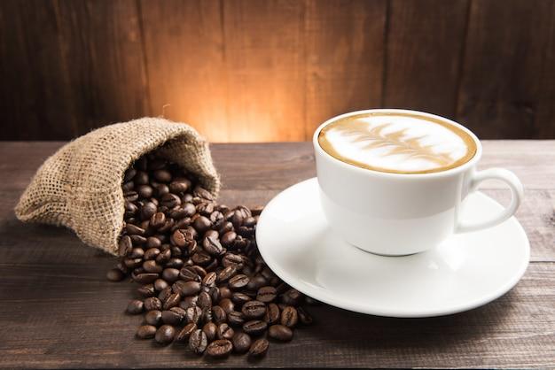 コーヒーカップと木製の背景のコーヒー豆。