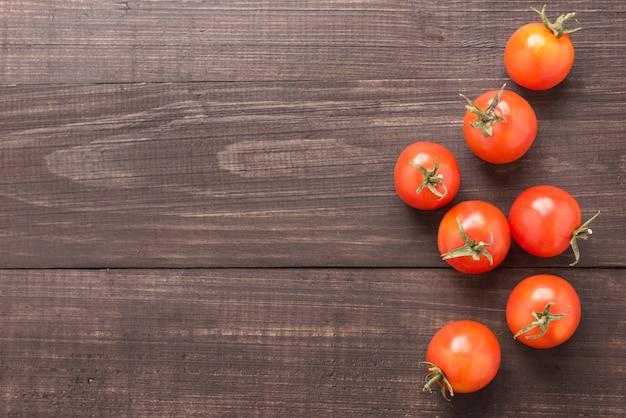 茶色の木製の背景にフレッシュトマト。上面図
