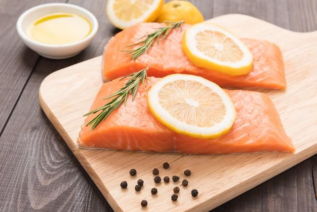 Свежий лосось и лимон на деревянном столе